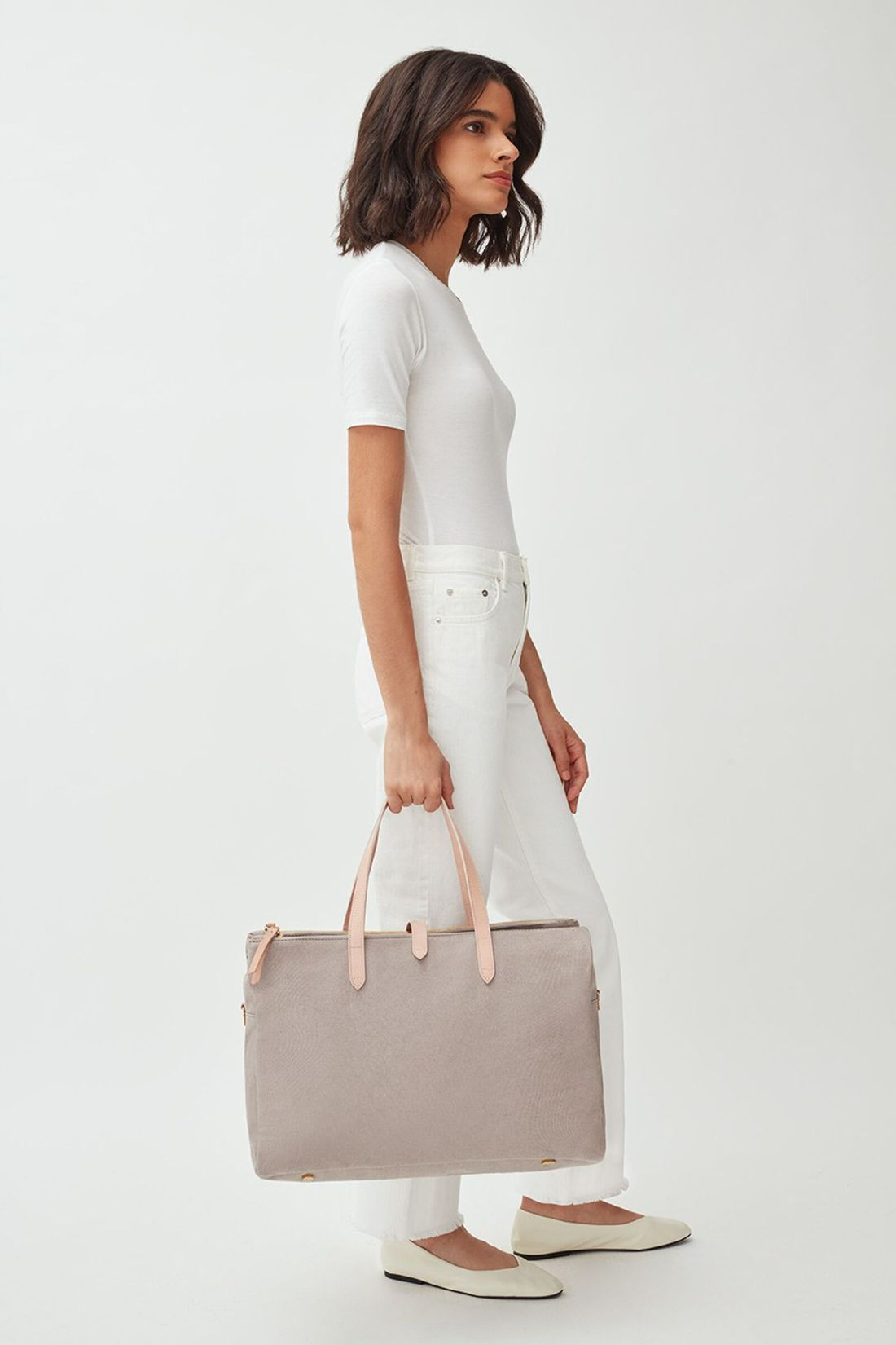 Modeling carrying Cuyana Triple Zipper Weekender Bag in Soft Grey Detail