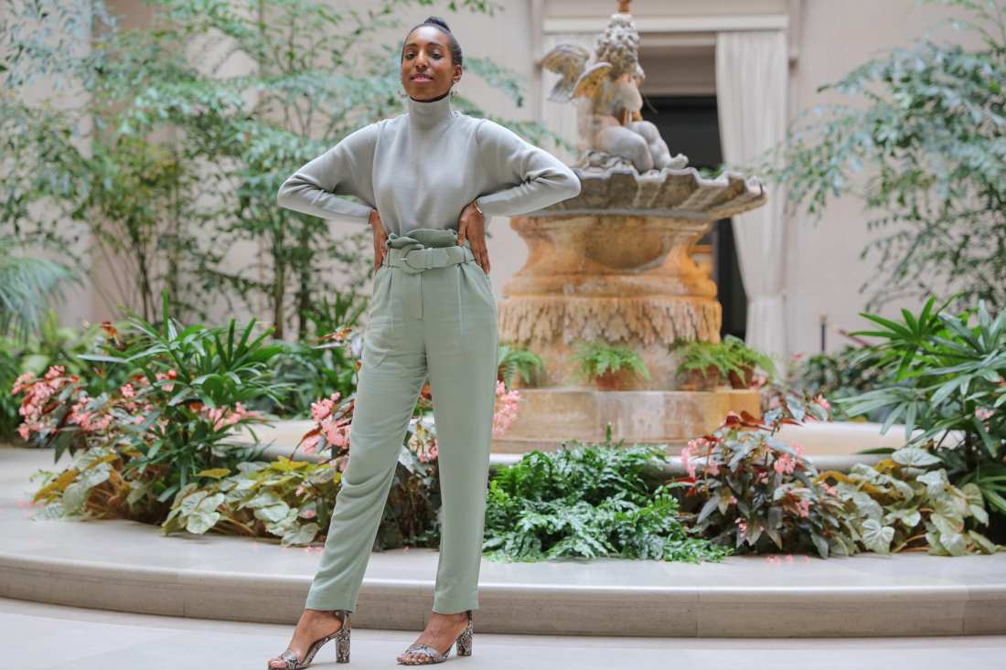 Lana Jackson stands in front of marble fountain wearing pistachio green sweater and pant outfit and snakeskin print heels