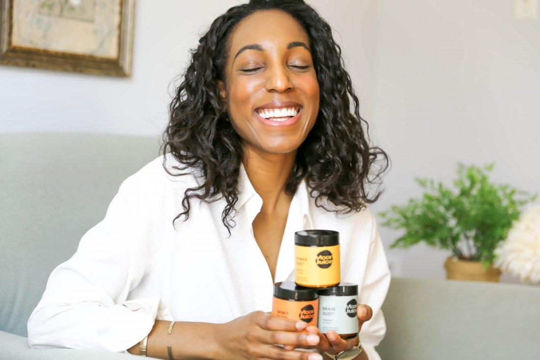 Lana Jackson laughs while holding three stacked jars of Moon Juice