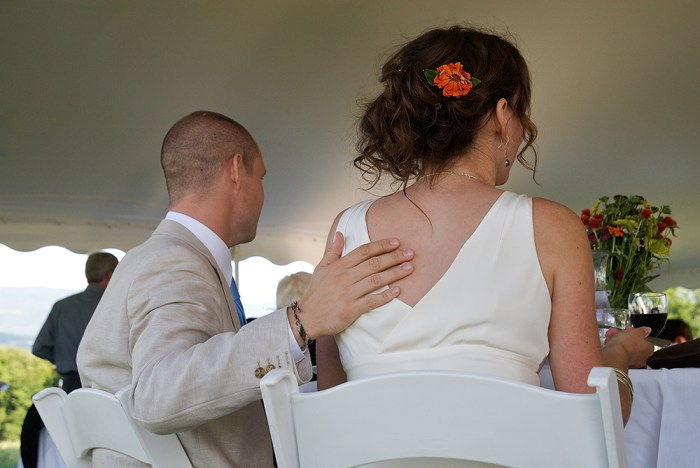 Groom tenderly touching his bride's bare back.