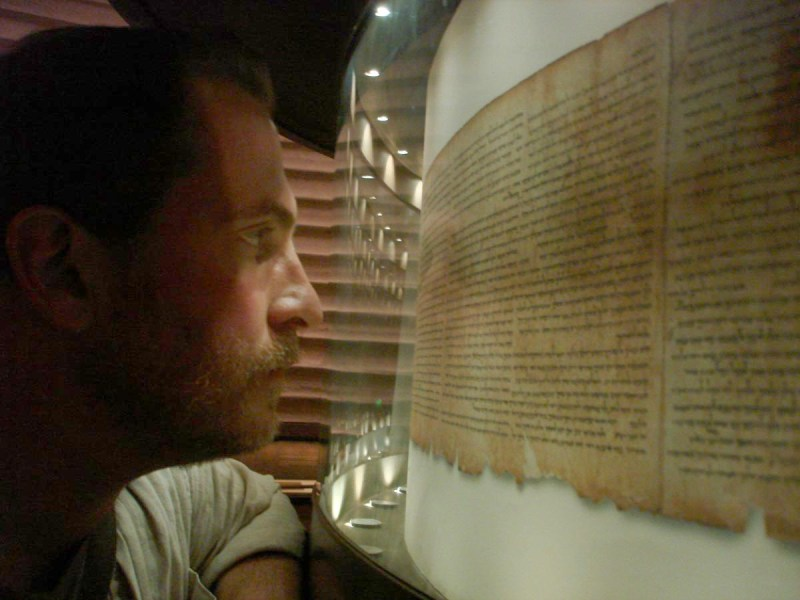 """Archaeologist Robert Cargill examines a full-scale facsimile of the 2000-year-old-plus Isaiah Scroll at Jerusalem's Shrine of the Book."" Photo © CTVC Ltd"
