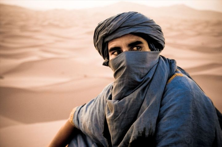 An Amazigh (Berber) man wearing a veil and turban in the desert.