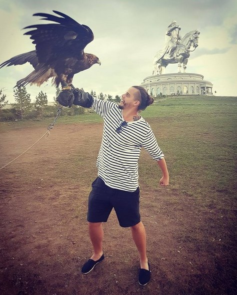 Ben Thomas in Mongolia, with a golden eagle and a giant statue of Genghis Khan.