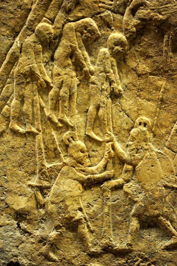 Assyrian soldiers impale prisoners