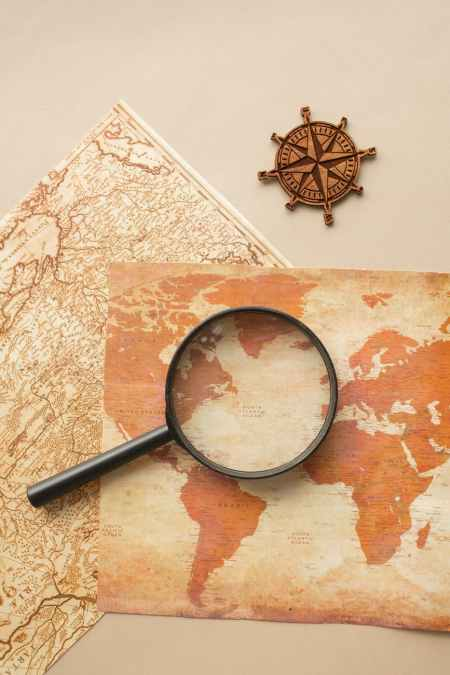 magnifying glass and wind rose on maps