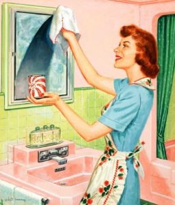 Woman smiles as she cleans her bathroom mirror