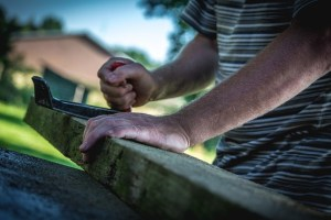man's hands working with plank of wood