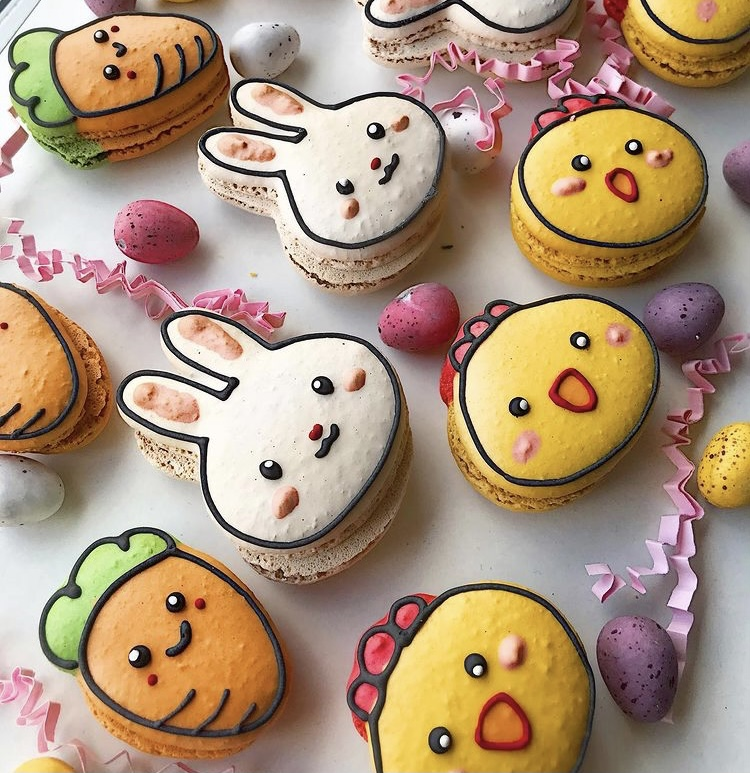 In this image, a variety of Easter macarons Arisa has made are on display. One of them is a carrot with a smiley face. Another one is a white bunny face. The last one is a yellow chick face.