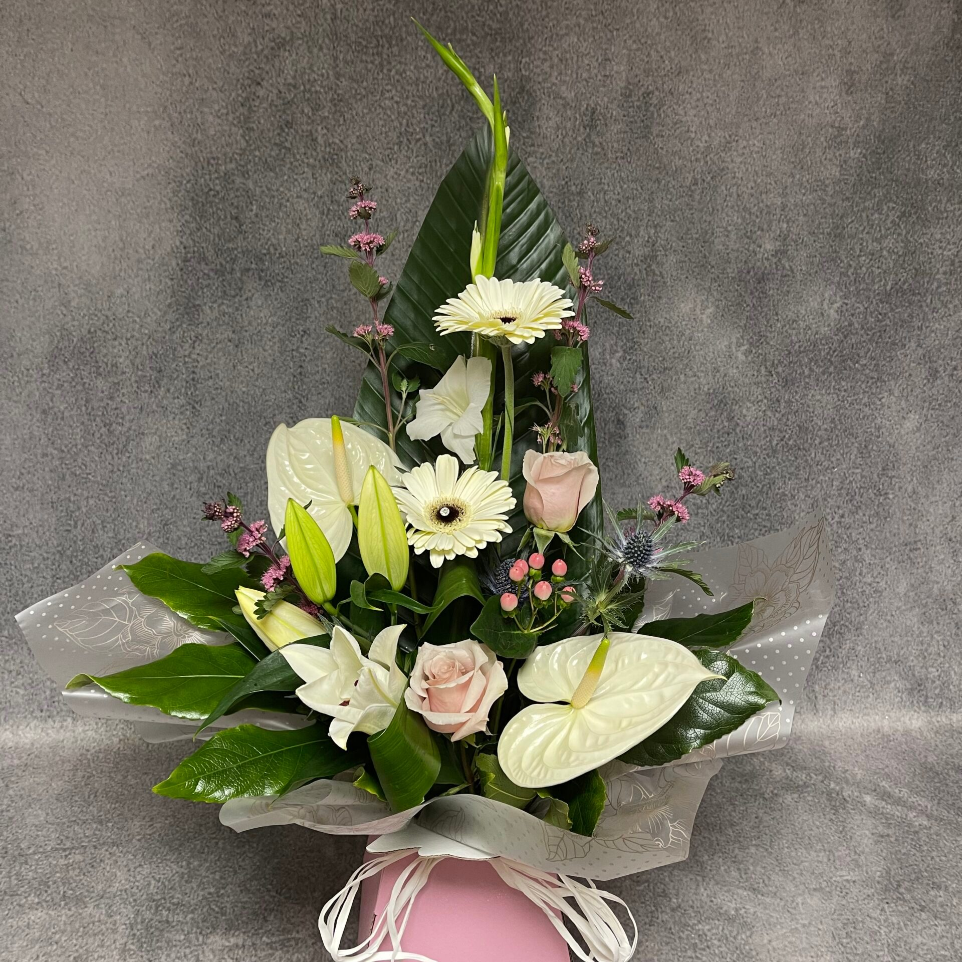 In this image, the bouquet has a somewhat triangular shape. It is in a small, pink box and big green leaves are the base for the bouquet. In the middle are a range of white flowers.