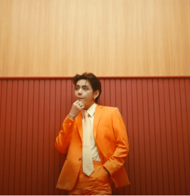 In this image, V from BTS is wearing an orange suit and is standing in an art deco deocrated elevator.