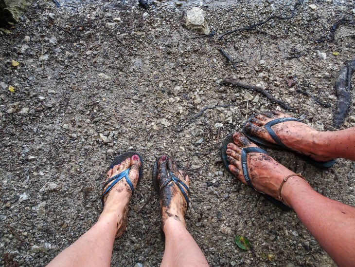 Two pairs of muddy feet standing on a dirt ground.