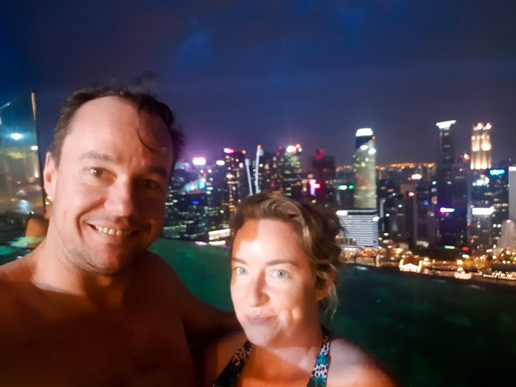 Keelie and Myles in the infinity pool, Singapore city by night in background