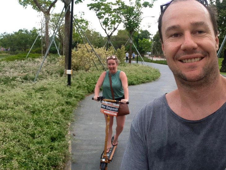 Myles and Keelie riding electric scooters through gardens on  the bay