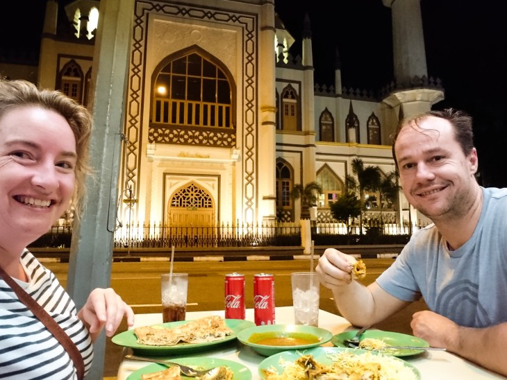 Keelie and Myles eating dinner in front of the Sultan Mosque