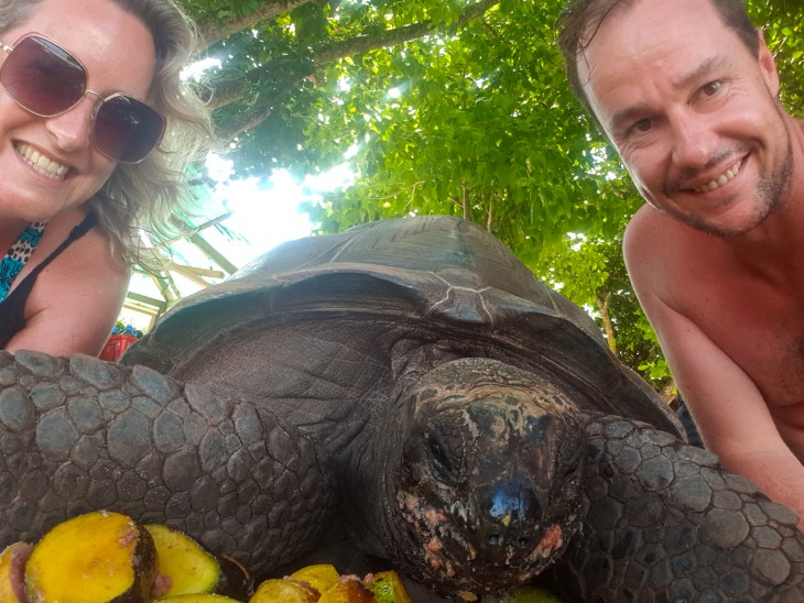 Keelie and Myles in a selfie with a tortoise eating fruit.