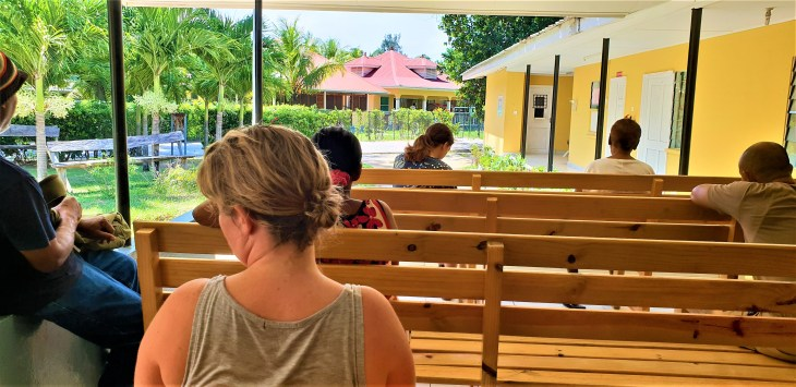 People sitting on wooden benches looking at a yellow building.