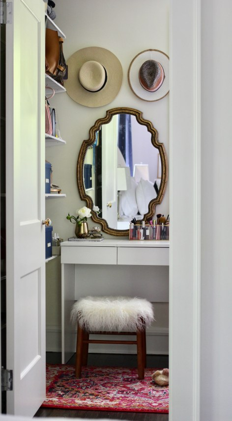 Small bedroom closet with white Ikea vanity and organized accessories.