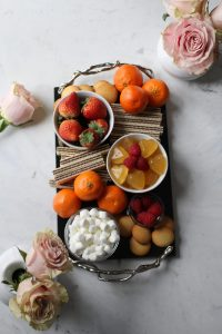 a dessert board on a marble table with pink roses featuring heart-shaped prosecco jello shots