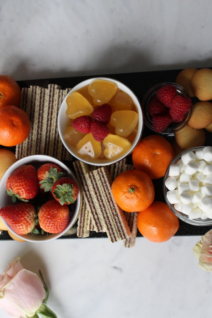 food board placed on marble table featuring fresh fruit, desserts and heart-shaped prosecco shots.