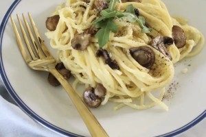 carbonara with parmigiano reggiano served on a white plate