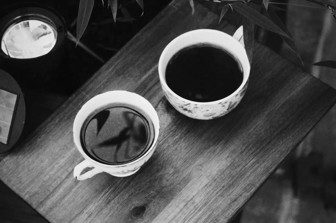 black and white photo of two coffee cups outside