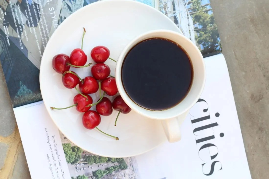 cup of coffee on a plate with cherries, for blog on dating an insecure person