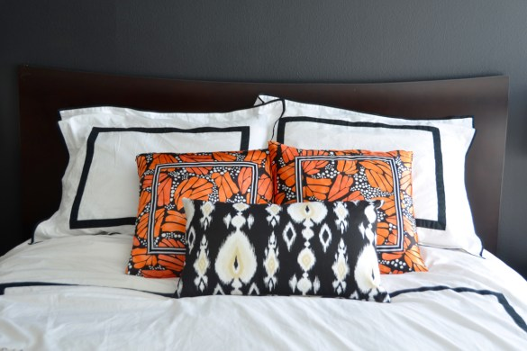mopboard black bedroom walls, bedroom renovation, orange butterfly pillows // thestylesafari.com