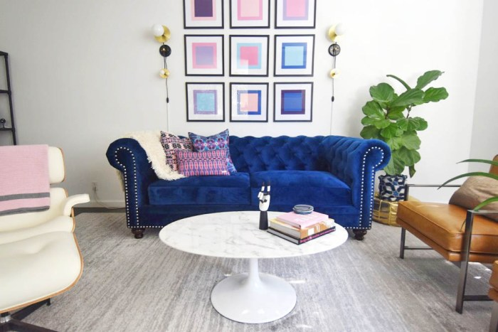 Midcentury glam living room, navy chesterfield sofa, saarinen tulip table, pop art, pink and blue, eames lounge chair
