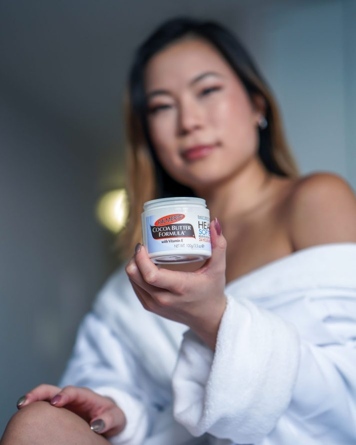 Kasey Ma Lifestyle Influencer of TheStyleWright Holds Palmer's Coconut Butter Formula Jar for dry skincare
