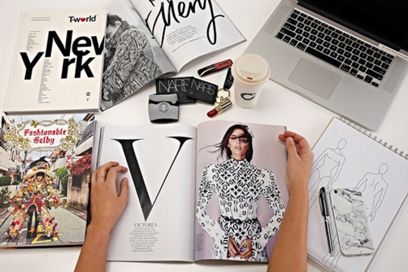 Open magazines laptop and makeup on table