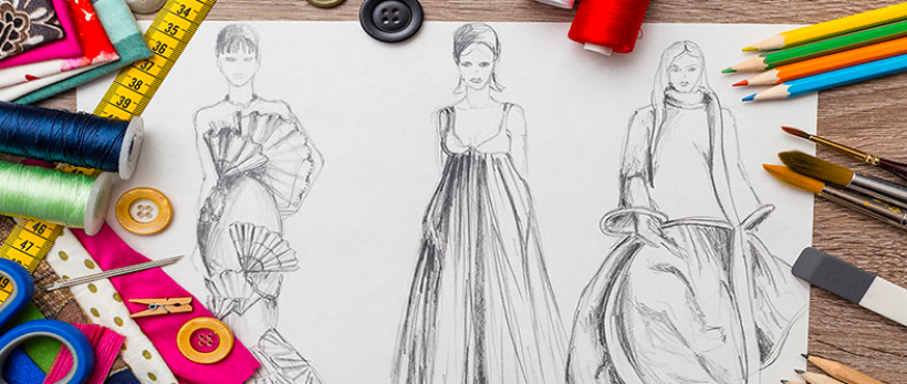 Fashion Design Sketches on Table with Colored Pencils and Stationary Tools