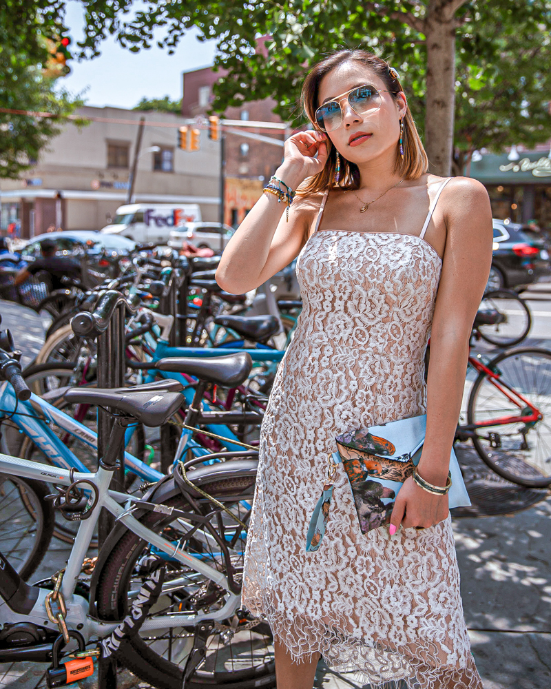 kasey ma of thestylewright wears an eliza j dress that is part of the nordstrom anniversary sale and early access sale standing in front of bikes in jersey city