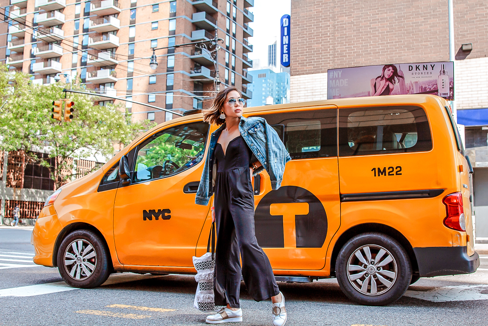 Kasey Ma of The StyleWright wearing strapless jumpsuit jean jacket standing in front of NYC taxi