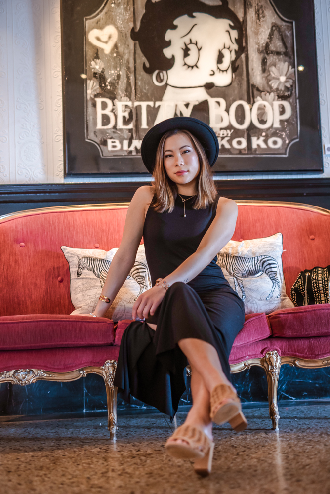 Kasey Ma of The StyleWright wearing black dress black hat sitting on red couch