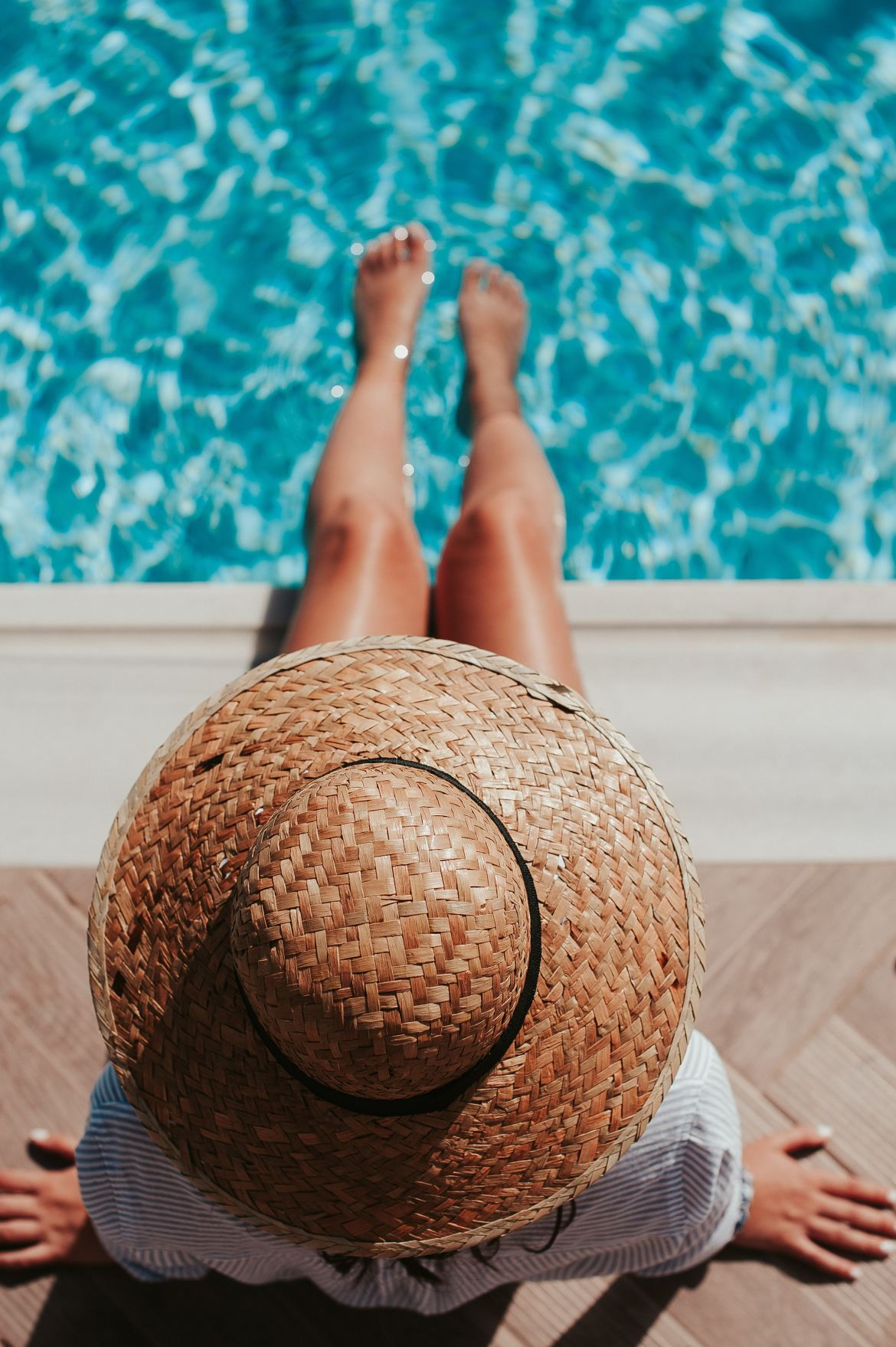 woman wearing hat sitting by the pool