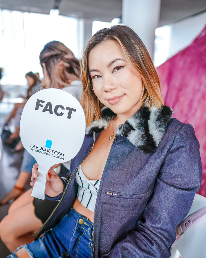 Kasey Ma holding up a acne treatment fact sign at La Roche-Posay's acne and dermatology class!