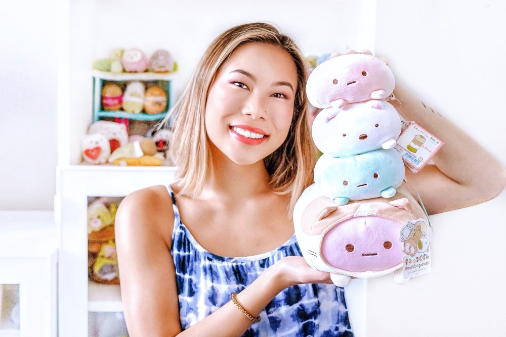 Kasey Ma holding up some of her beloved Sumikko Gurashi plushies