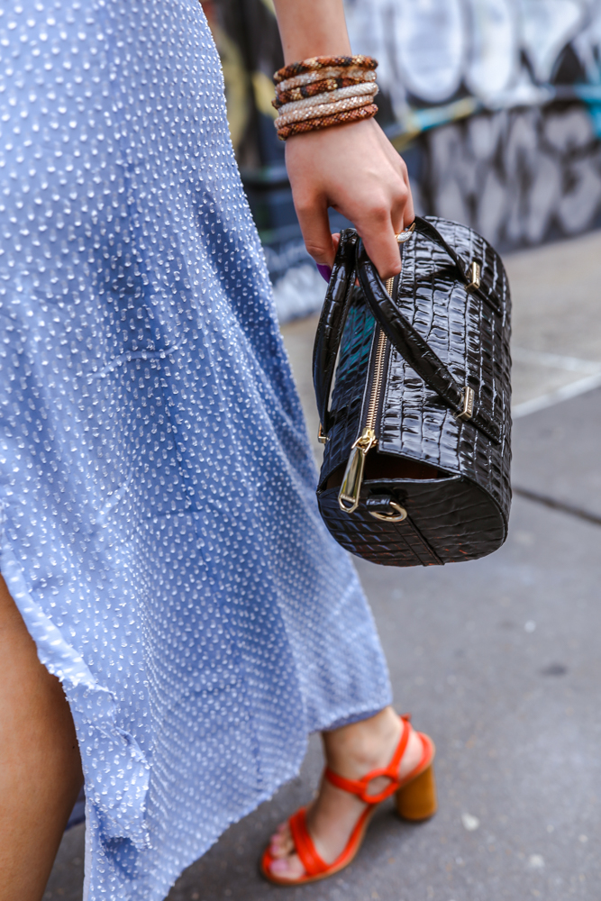 Kasey Ma of TheStyleWright with a black statement bag and blue dress talks about how to dress