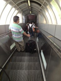 A load of people were walking down a set of stairs, I took the escalator and first class seats.