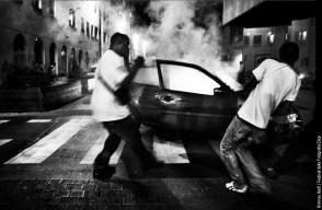 Saint Denis, Regione dell' Île-de-France, Francia, 13 luglio 2007. Un gruppo di uomini lanciano potenti petardi all'interno di un'auto per darla alle amme nelle strade di Saint Denis nel giorno della Festa Nazionale. I petardi sono usati in segno di protesta per essere lanciati addosso alla polizia durante gli scontri nelle periferie. © Arnau Bach