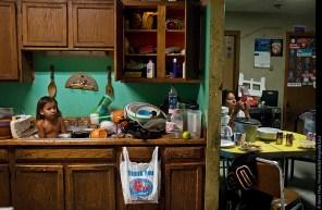 Il piccolo C.J. Shot, tre anni, fa il bagno tra i piatti. Il concetto oglala di tiospaye – l'unità della famiglia allargata – e la carenza di alloggi nella riserva fa sì che le case siano spesso sovraffollate. Nel 2008, quando è stata scattata la foto, in questa abitazione con tre stanze da letto vivevano in 22. «Queste case non hanno nulla a che fare con noi» dice l'attivista Alex White Plume. © Aaron Huey