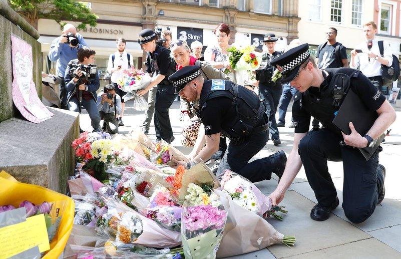 Poliziotti depongono fiori per le vittime dell'attacco terroristico alla Manchester Arena / Foto via Twitter