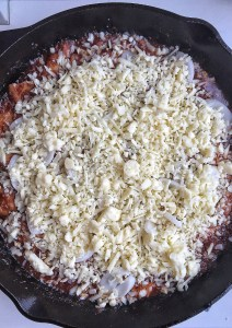 cheese covered dish in cast iron skillet