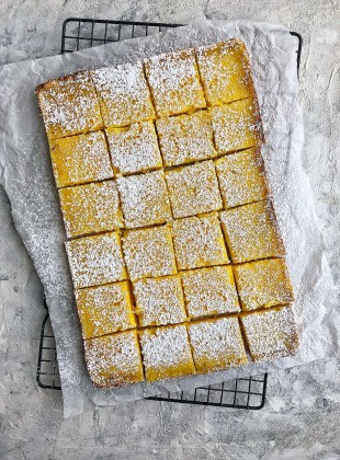 lemon bars on top of parchment paper and cooling rack