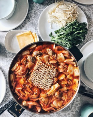 budae jjigae ingredients in hot pot on table with plate of vegetables on the side