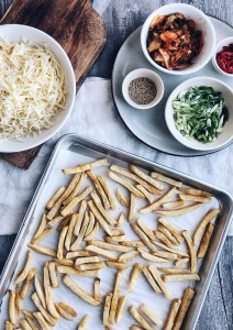 french fries on sheet pan with kimchi and cheese on the side