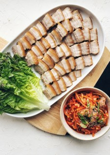 Korean bo ssam on round cutting board with lettuce wraps and oyster radish kimchi