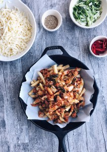 french fries covered in cooked kimchi with bowl of cheese on the side
