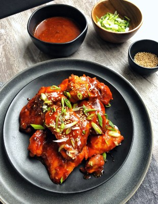 gochujang chicken on black plate with extra side in bowl on side