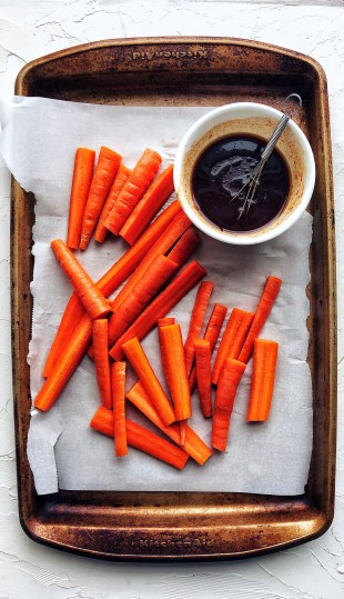 raw carrots and gochujang sauce on sheet pan with parchment paper